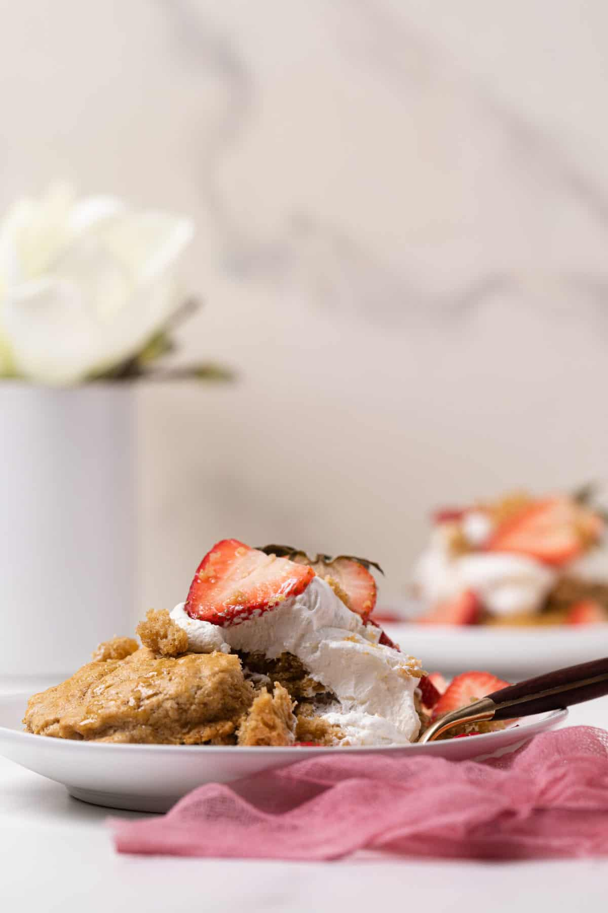 Maple Whole Wheat Oatmeal Strawberry Shortcake on a white plate with a white flour in the background and pink gauze