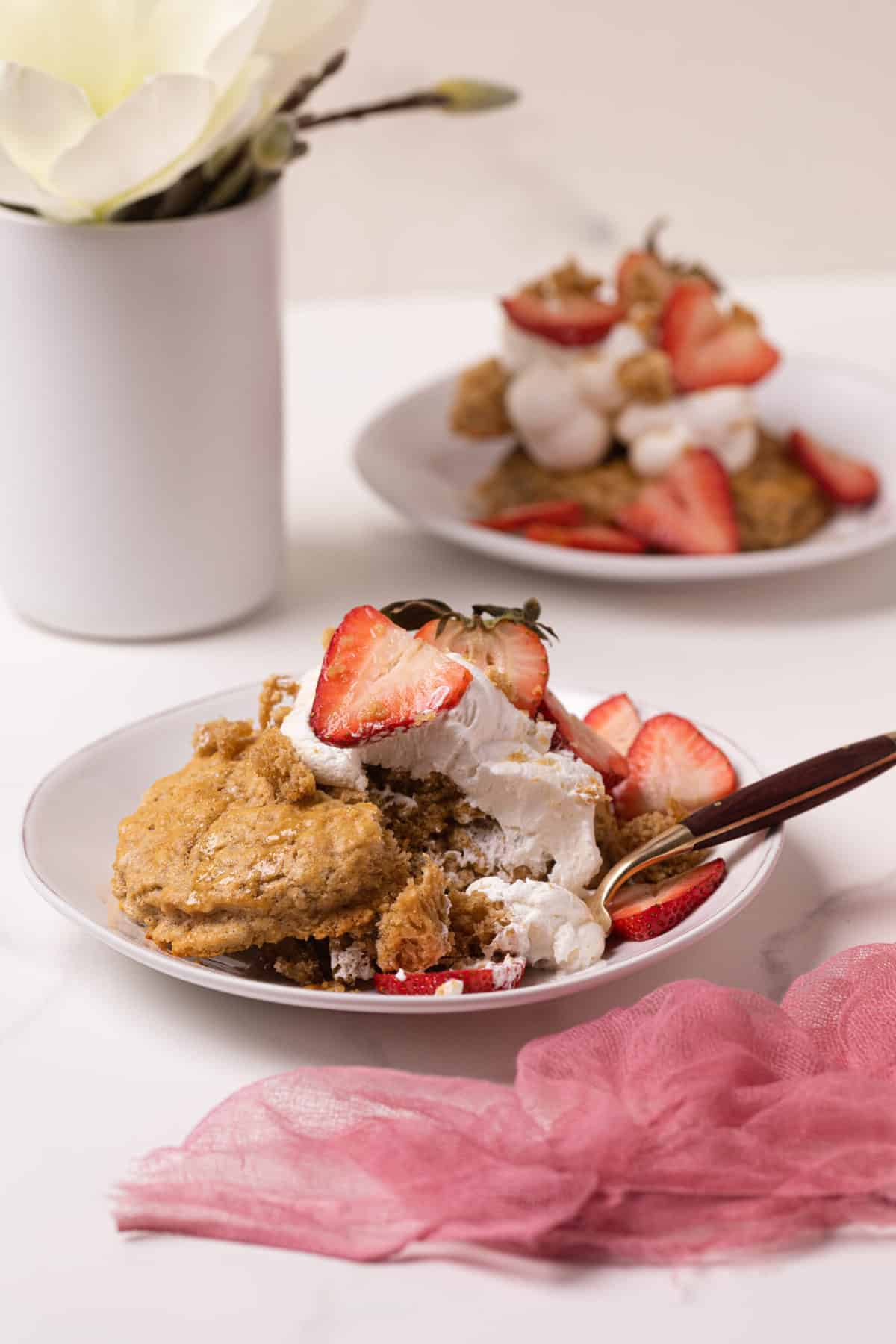 close up on Maple Whole Wheat Oatmeal Strawberry Shortcake on a white plate with a white flour in the background and pink gauze