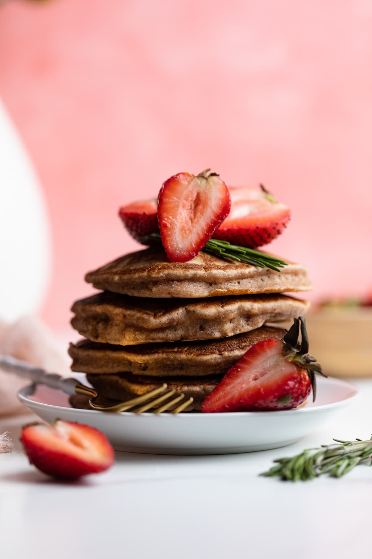 Perfect Whole Wheat Strawberry Pancakes in a stack on a plate with fresh strawberries
