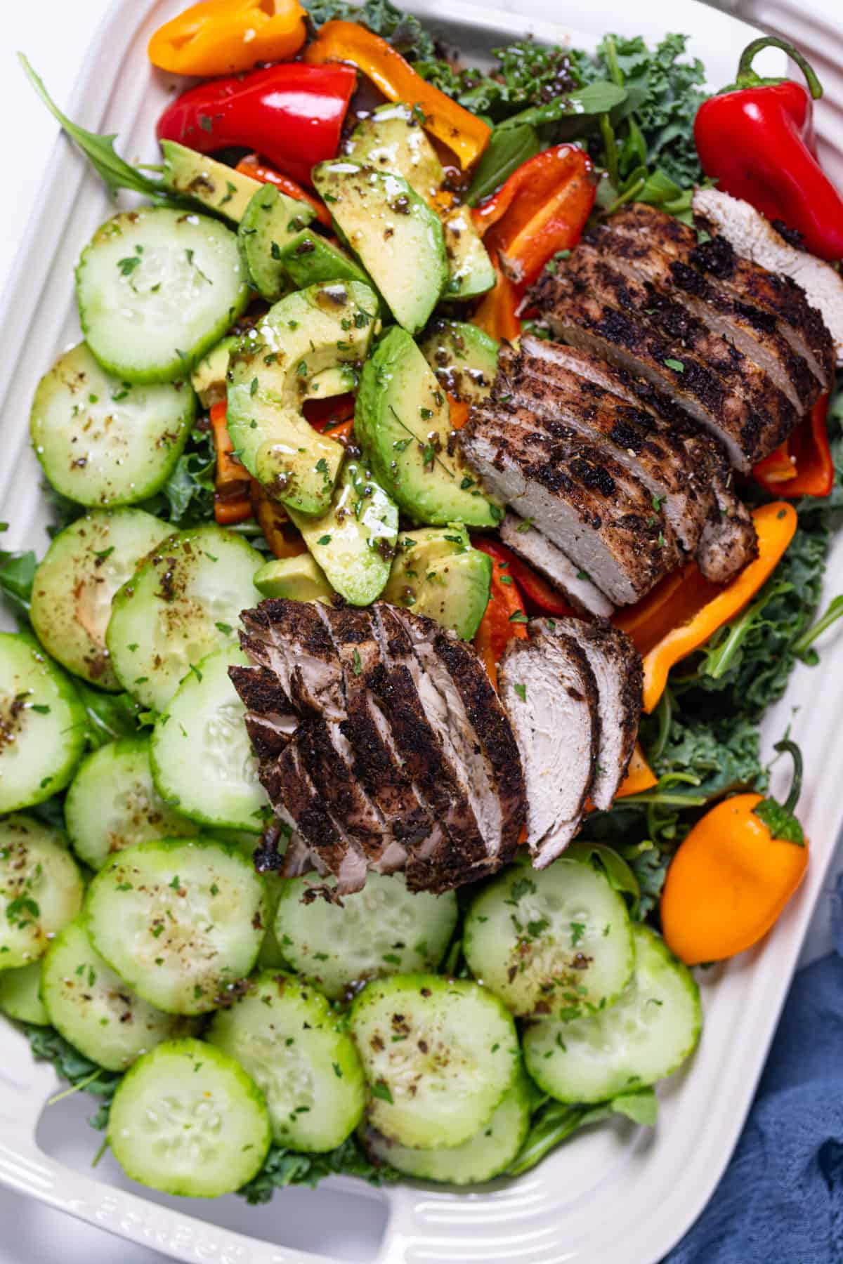 Oven Baked Jamaican Jerk Chicken Salad on a white serving platter with cucumber and peppers