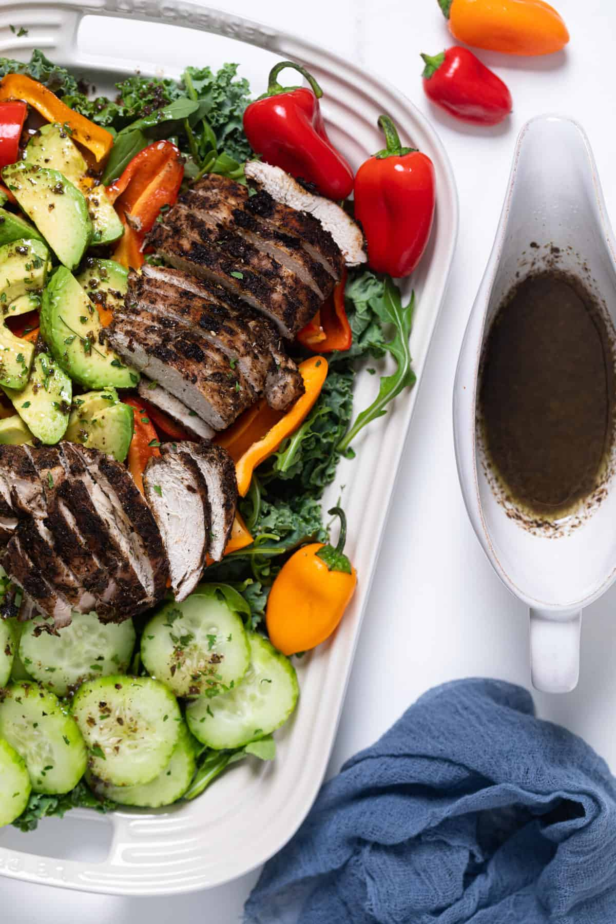 Oven Baked Jamaican Jerk Chicken Salad on a white serving platter with dressing in a pitcher on the side