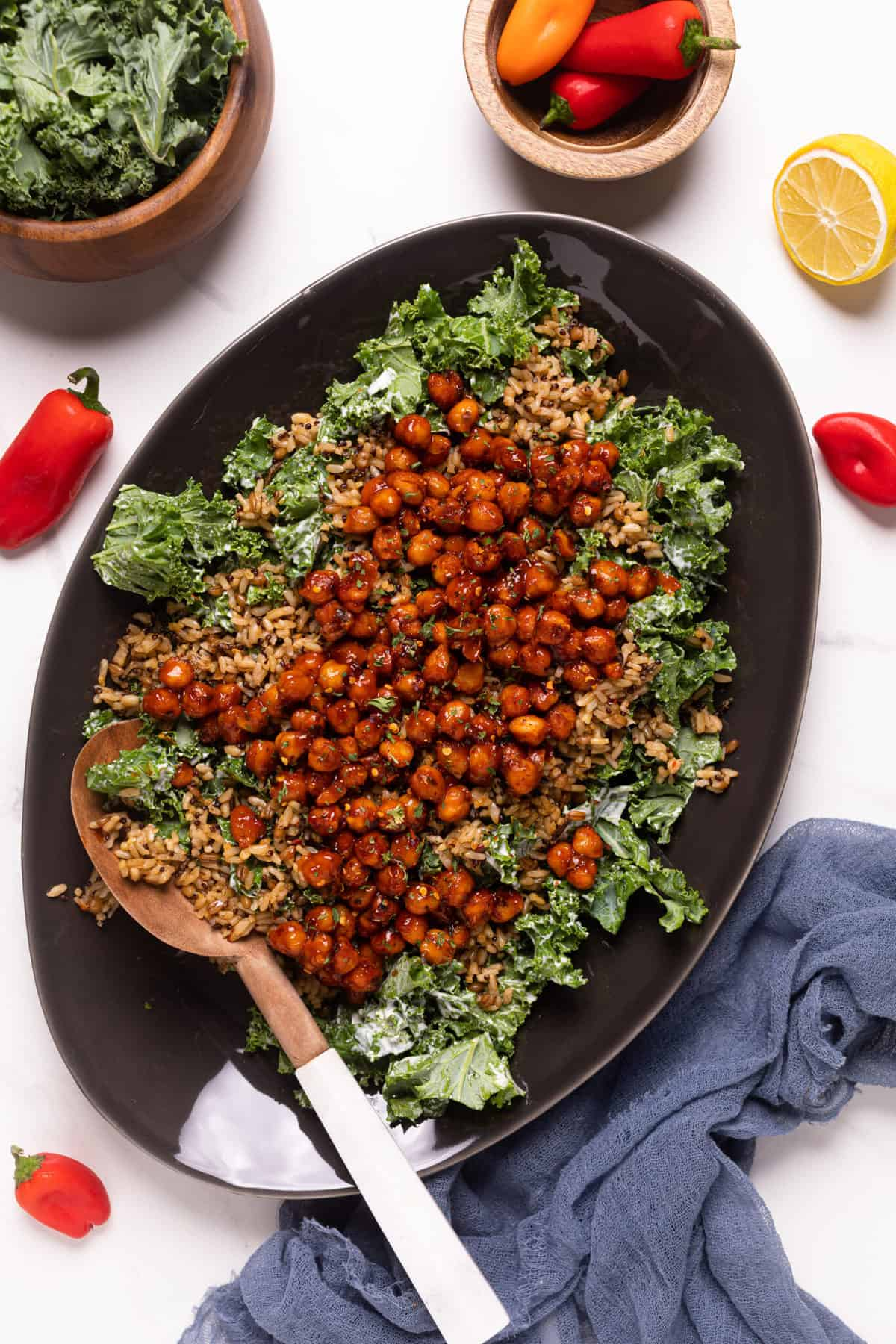 Healthy Loaded Kale Salad with Spicy Chickpeas on a black serving platter with fresh peppers on the side