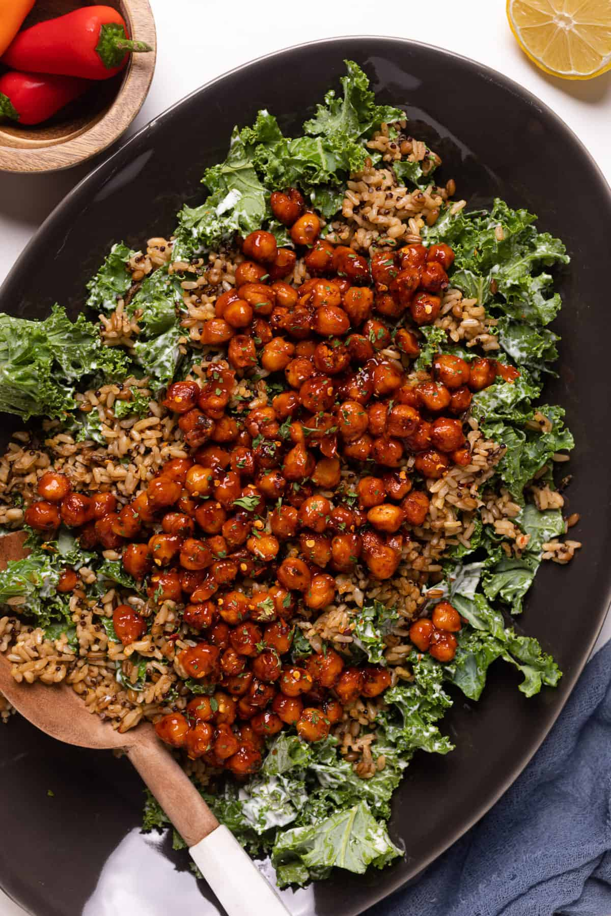 Healthy Loaded Kale Salad with Spicy Chickpeas on a black serving platter