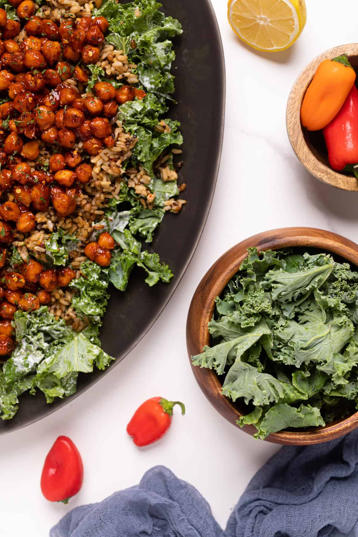 Healthy Loaded Kale Salad with Spicy Chickpeas on a black serving platter with a wooden bowl of fresh kale on the side