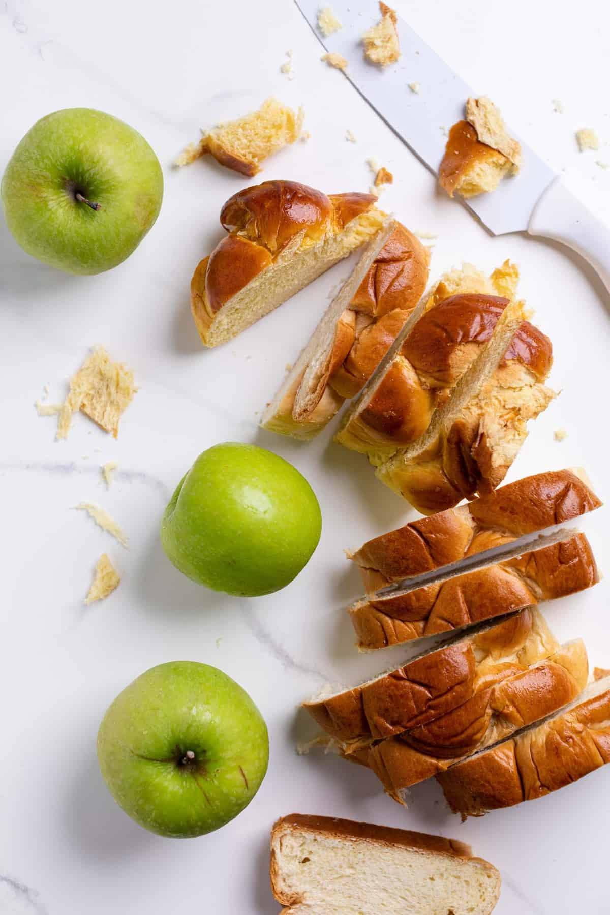 overhead of slices of challah bread and wgreen apples on a marble counter