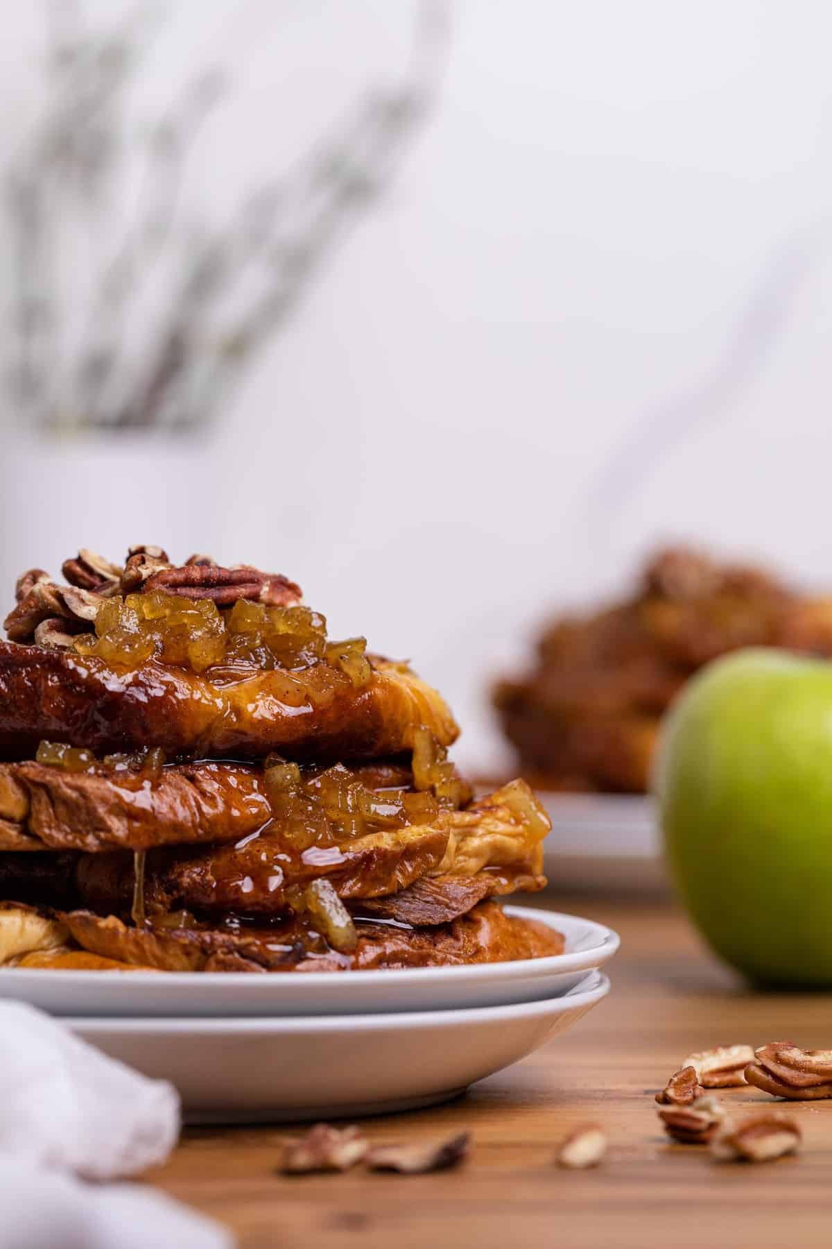 Caramelized Apple French Toast slices on two white plates with a green apple on the side
