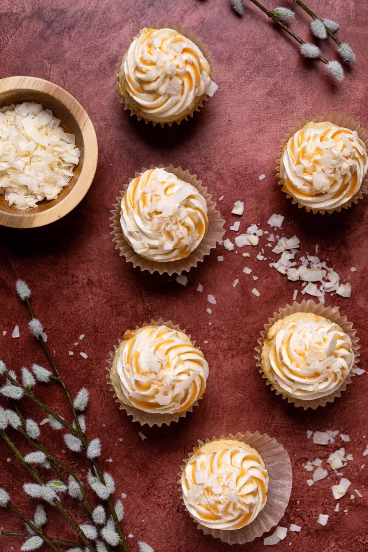 Easy Caramel Coconut Cupcakes in paper wrappers on a red surface with coconut flakes