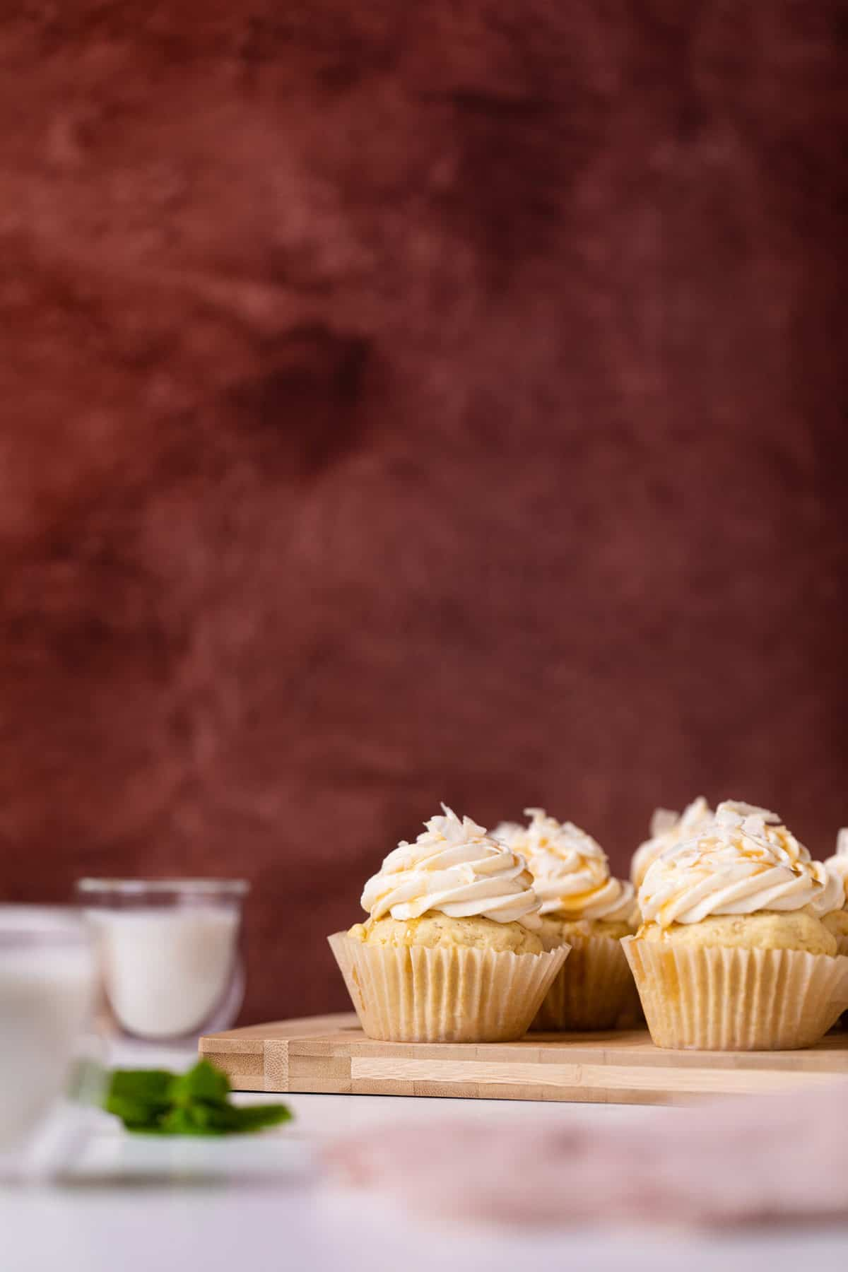 Easy Caramel Coconut Cupcakes in paper wrappers on a white surface on a cutting board