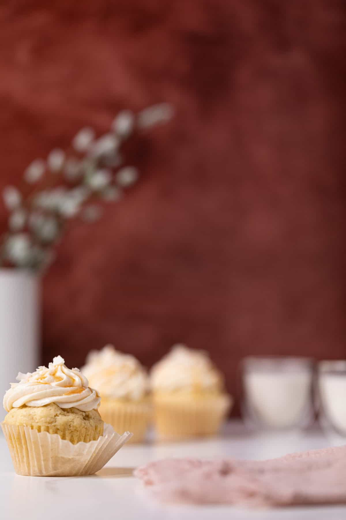 Easy Caramel Coconut Cupcakes in paper wrappers on a white surface with a red background
