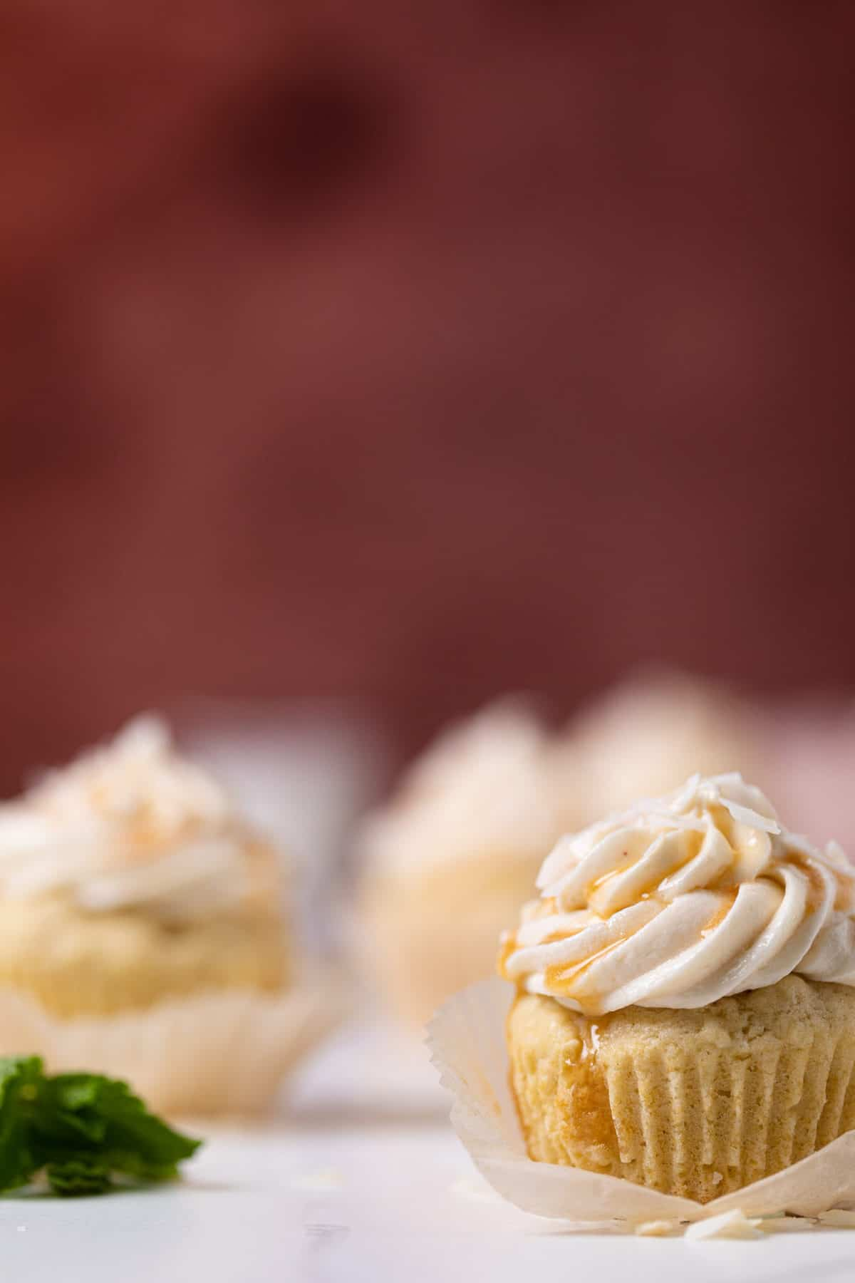 Easy Caramel Coconut Cupcakes in paper wrappers on a white surface