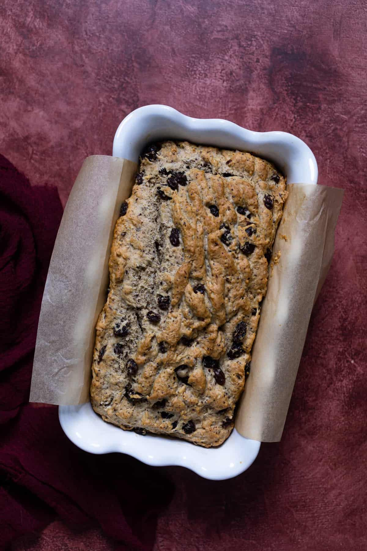 Homemade Rum Raisin Bread in a white baking dish with parchment paper on the sides