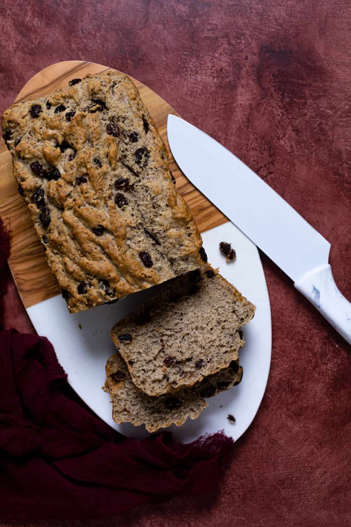 Homemade Rum Raisin Bread on a cutting board with a white knife