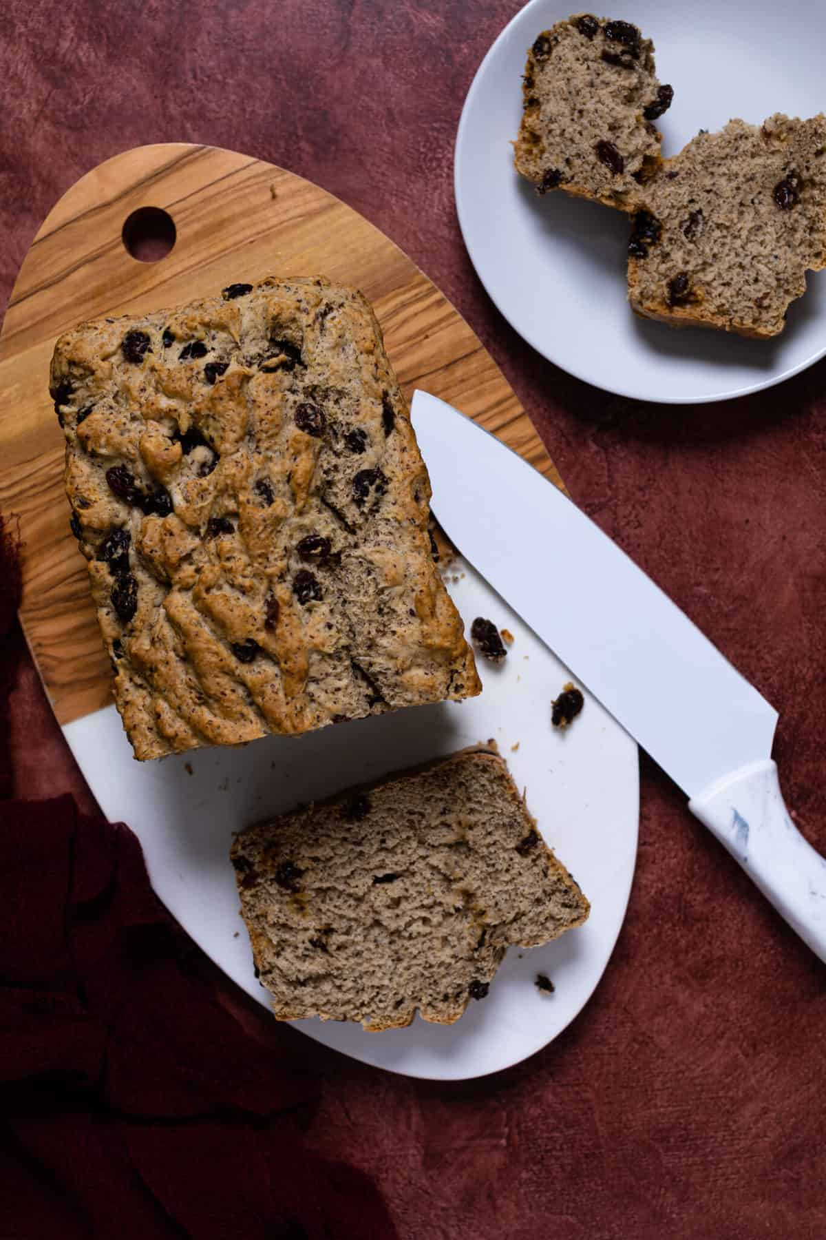 Homemade Rum + Raisin Bread on a wooden cutting board with a slice cut away