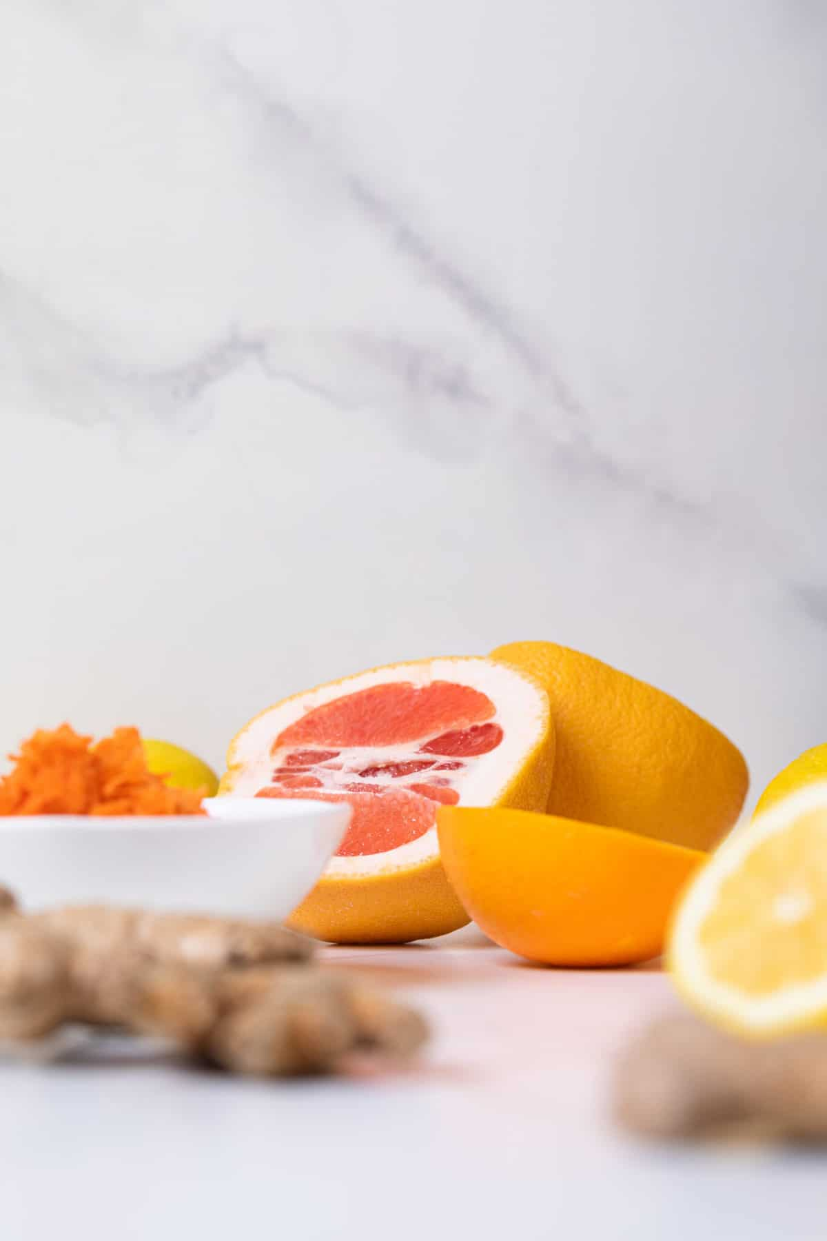 fresh orange slices and ginger root on a marble background