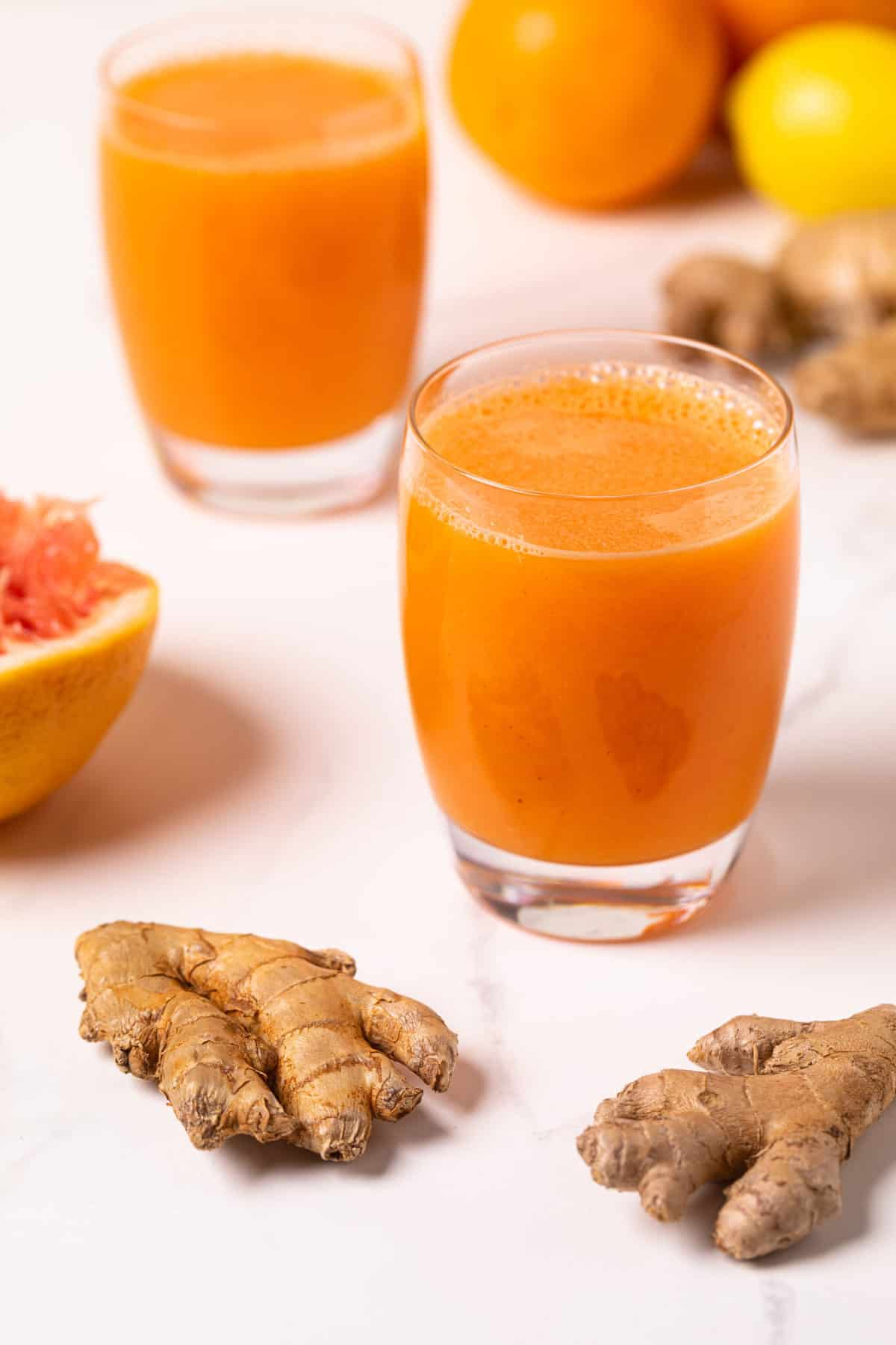 Carrot Ginger Citrus Turmeric Juice in a glass with fresh ginger root