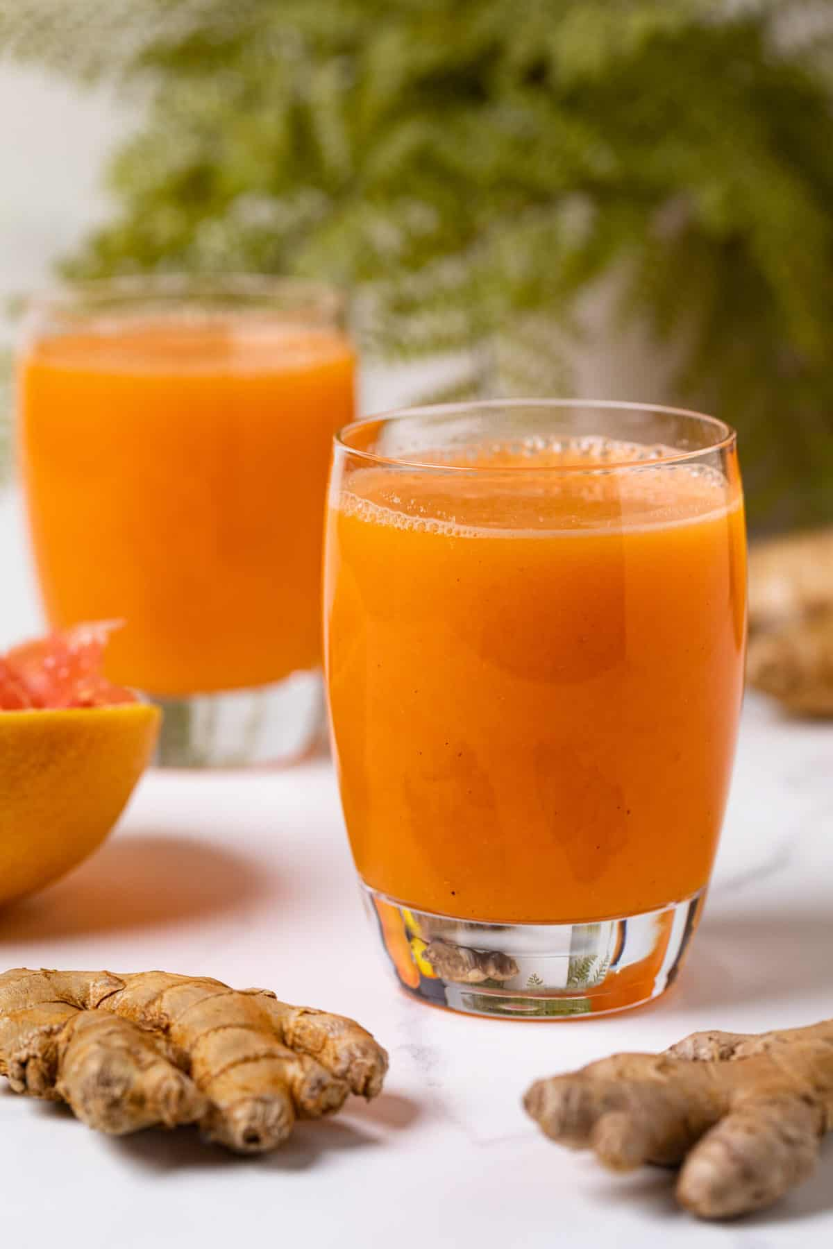 two glasses of Carrot Ginger Citrus Turmeric Juice with raw turmeric roots