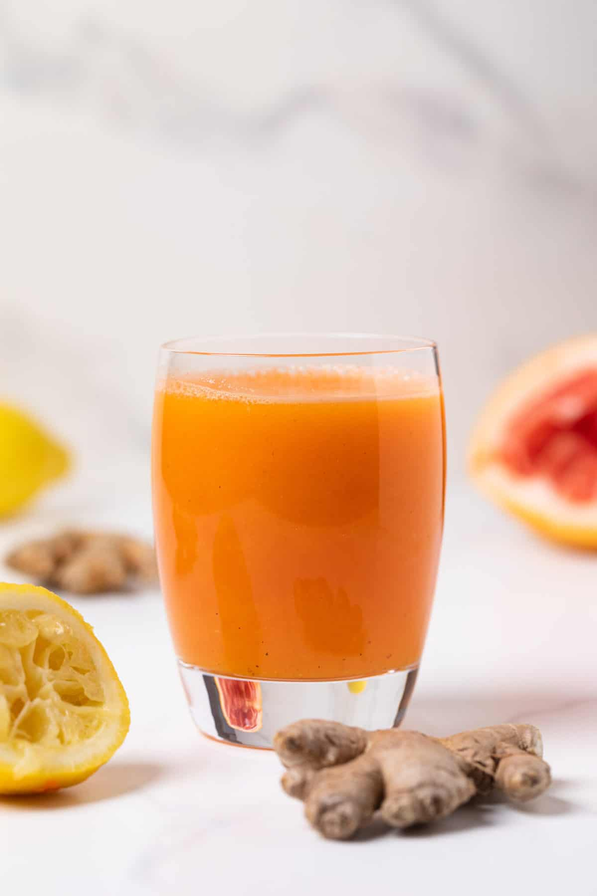 Carrot Ginger Citrus Turmeric Juice in a glass with fresh ginger root and orange slices