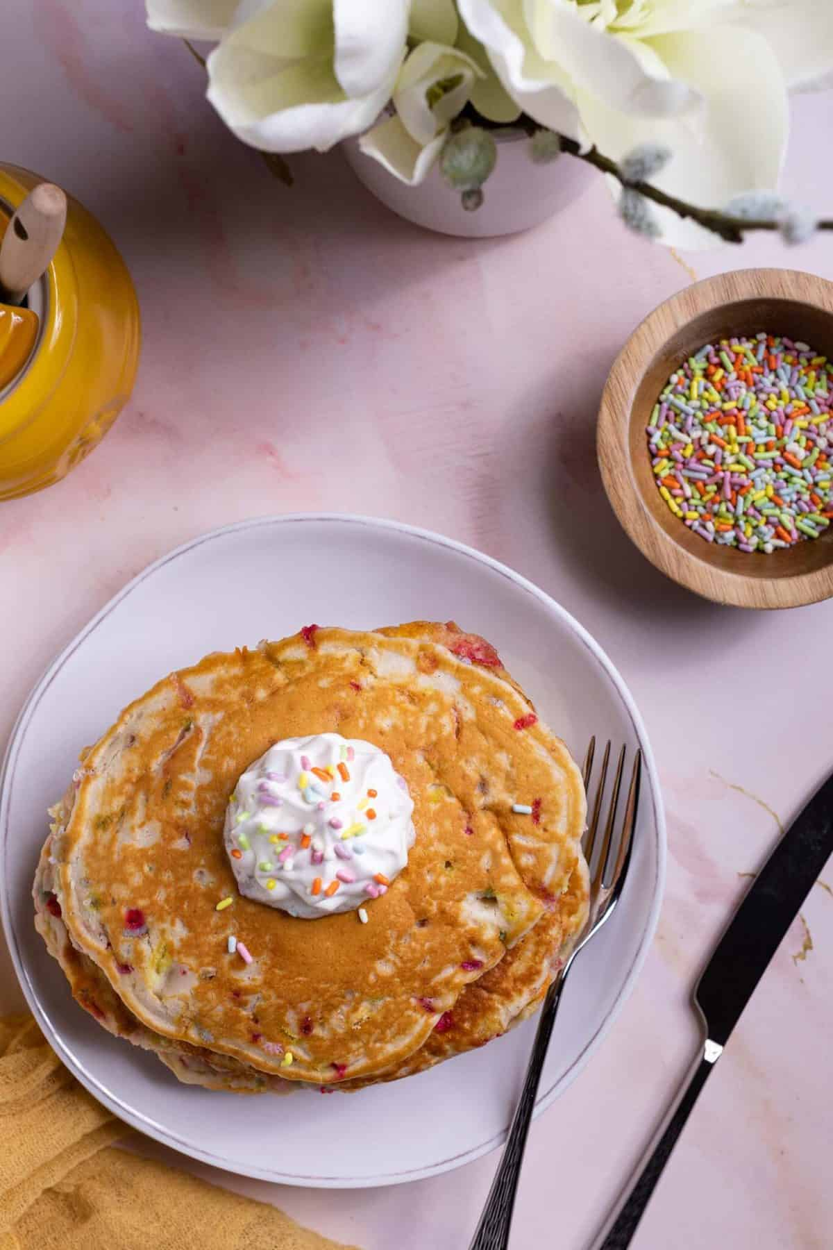 overhead of Quick + Easy Funfetti Vegan Pancakes in a stack with whipped cream on top and a fork and knife