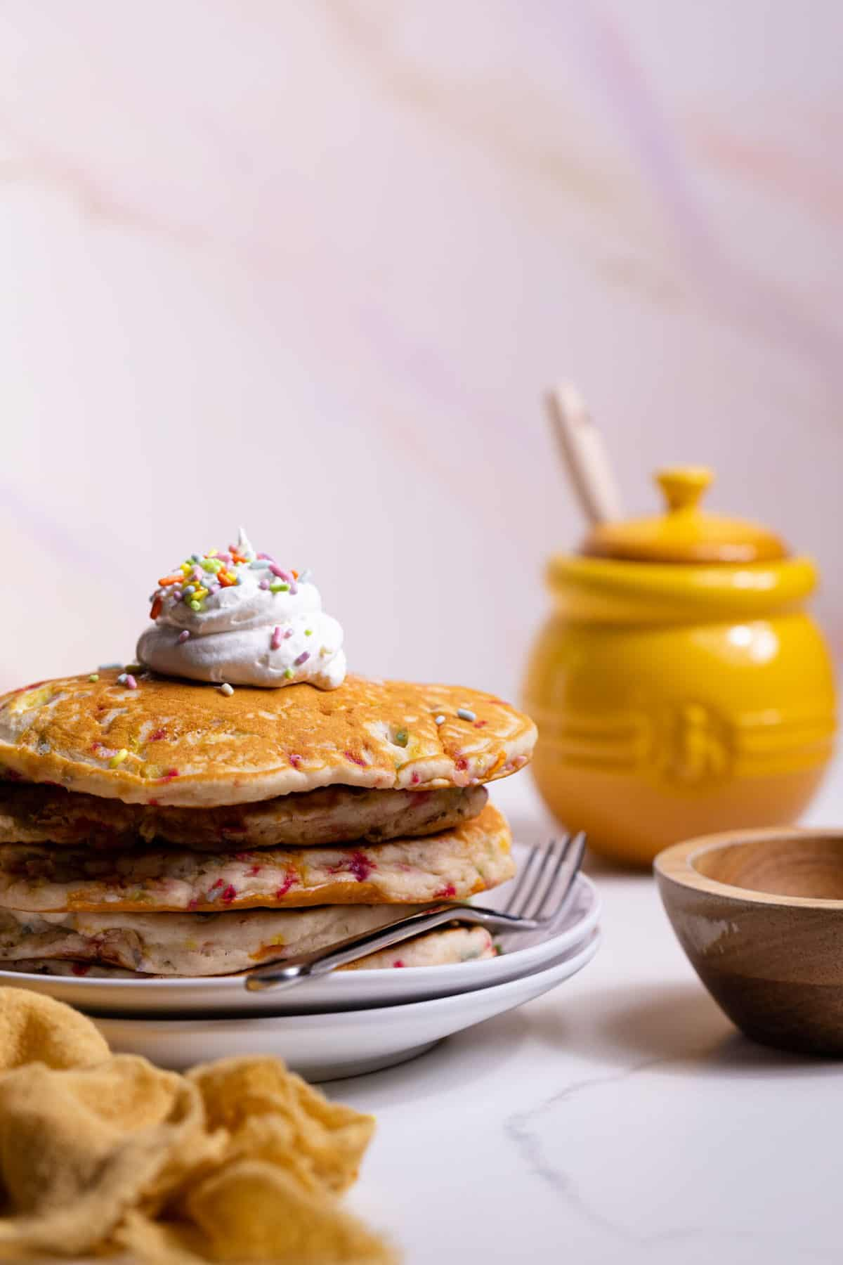 Quick + Easy Funfetti Vegan Pancakes in a stack with whipped cream on top and a fork