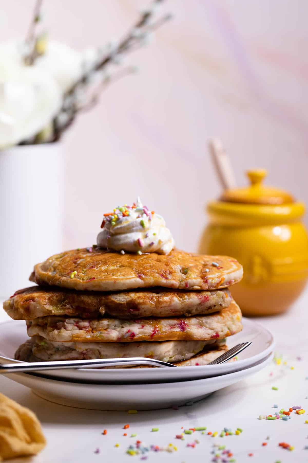 Quick + Easy Funfetti Vegan Pancakes stacked on two white plates with white frosting on top