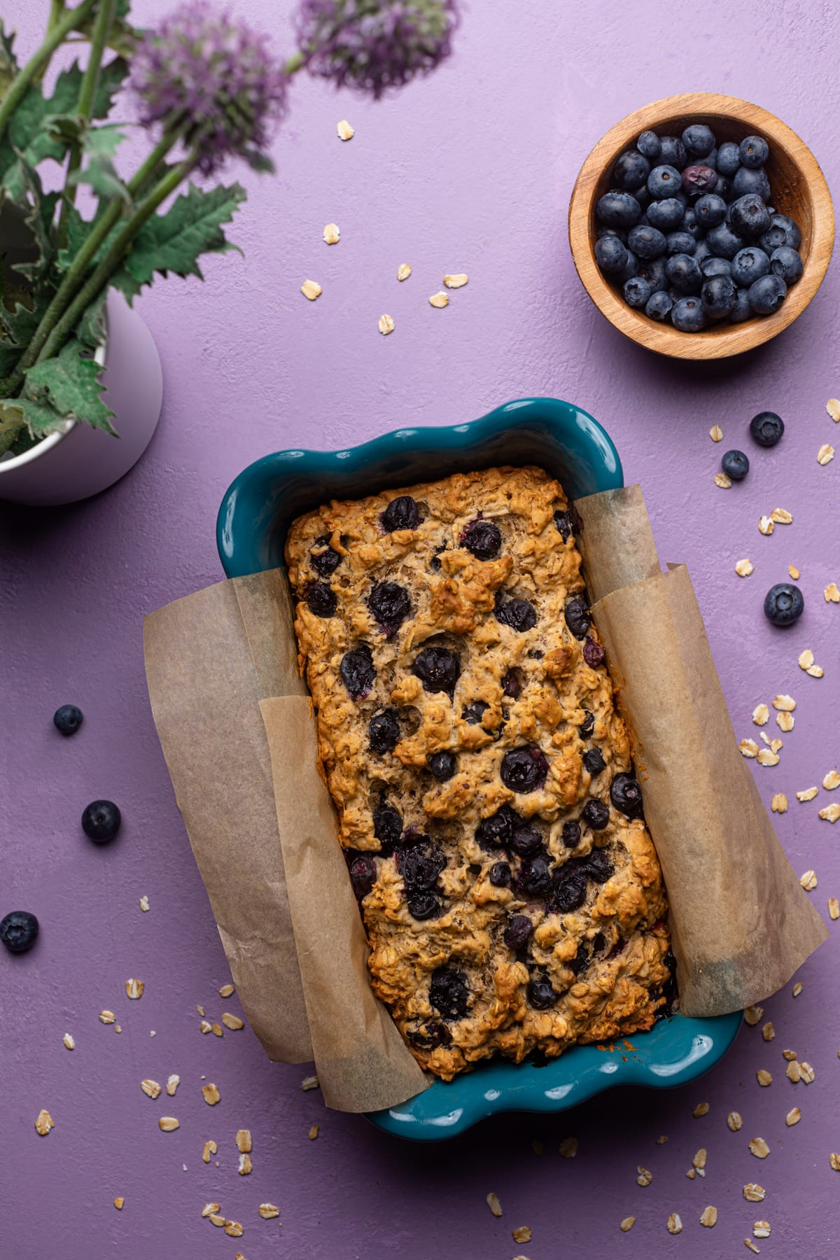 Healthy Blueberry Oatmeal Breakfast Bread in a loaf pan with fresh flowers