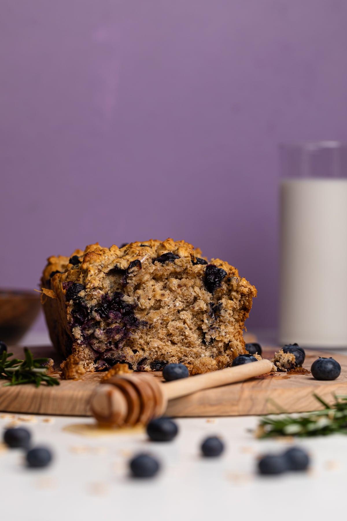 Healthy Blueberry Oatmeal Breakfast Bread cut in half on a cutting board
