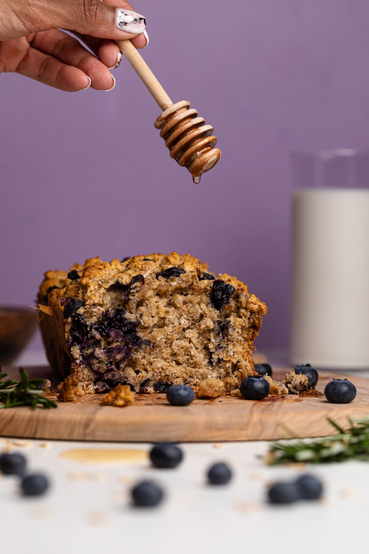 Healthy Blueberry Oatmeal Breakfast Bread loaf with honey being drizzled on top