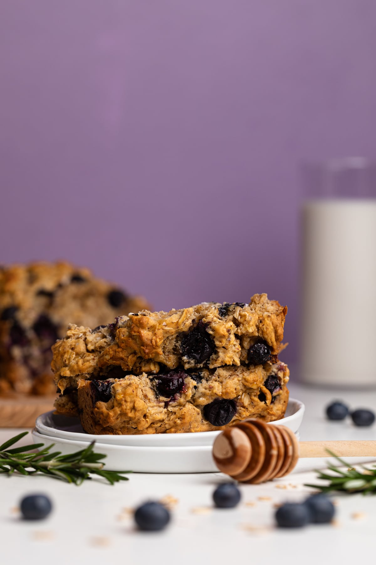 Healthy Blueberry Oatmeal Breakfast Bread slices on a plate with fresh berries and rosemary