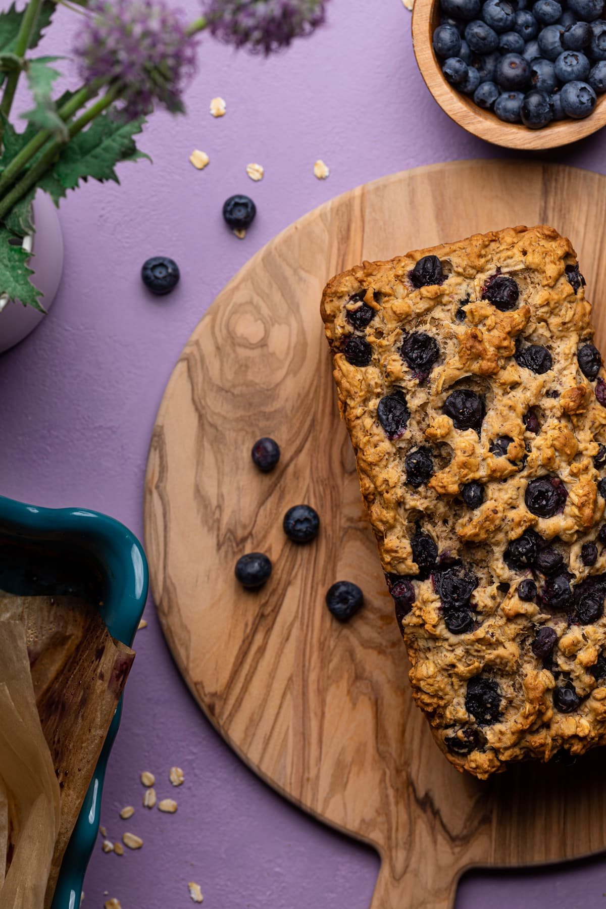 Healthy Blueberry Oatmeal Breakfast Bread with fresh berries on a cutting board