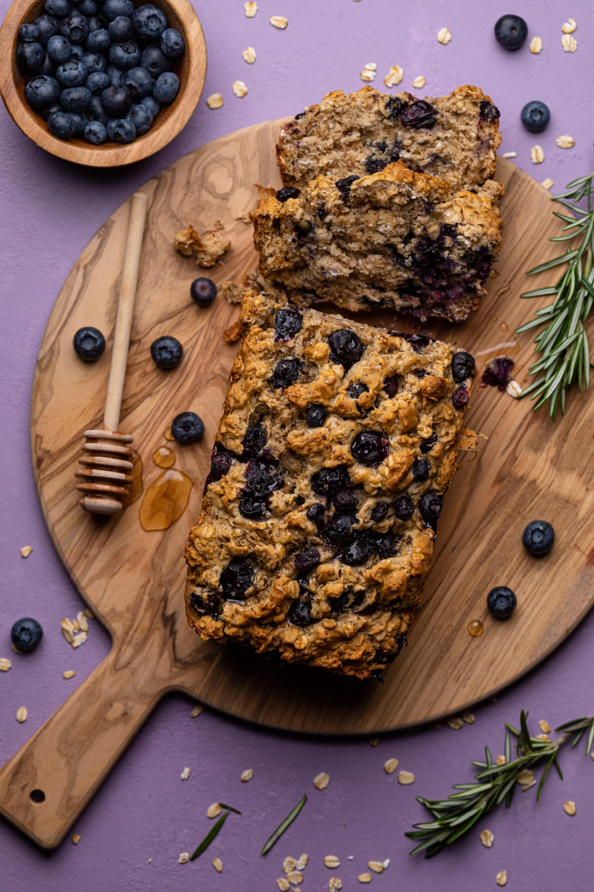 Healthy Blueberry Oatmeal Breakfast Bread on a cutting board with a honey stirrer