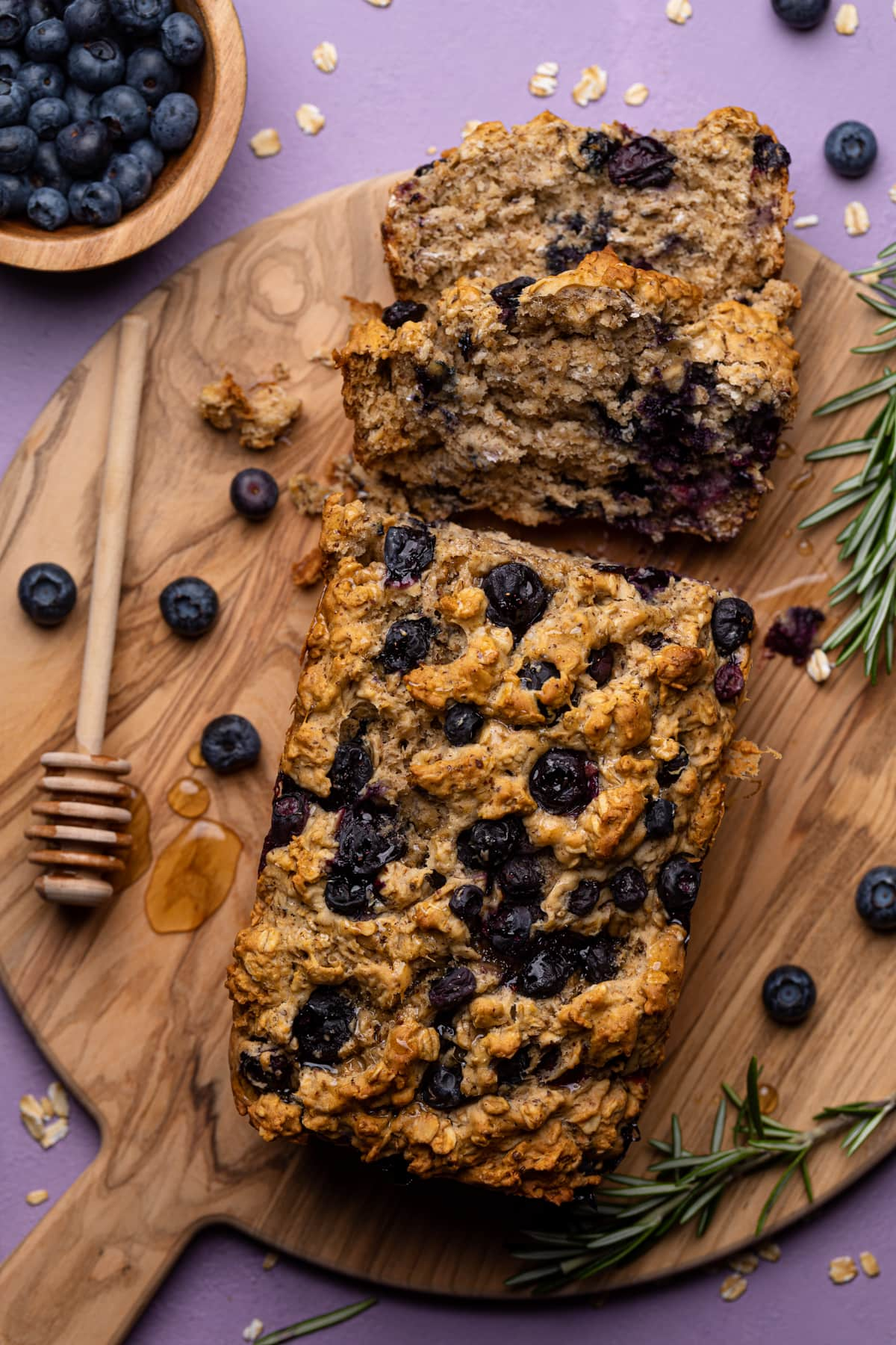 Healthy Blueberry Oatmeal Breakfast Bread with slices removed on a wooden cutting board