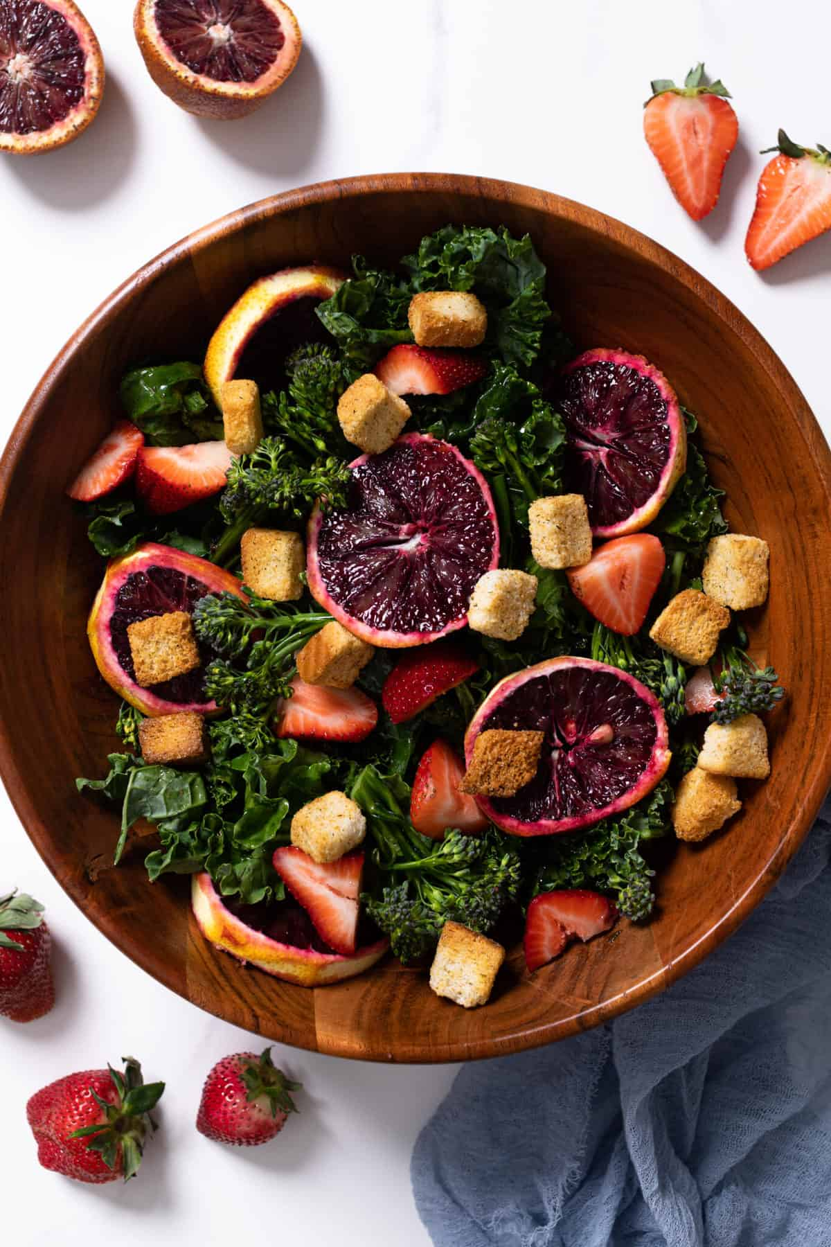 overhead of a bowl of blood orange kale salad with strawberries with a gold fork and croutons