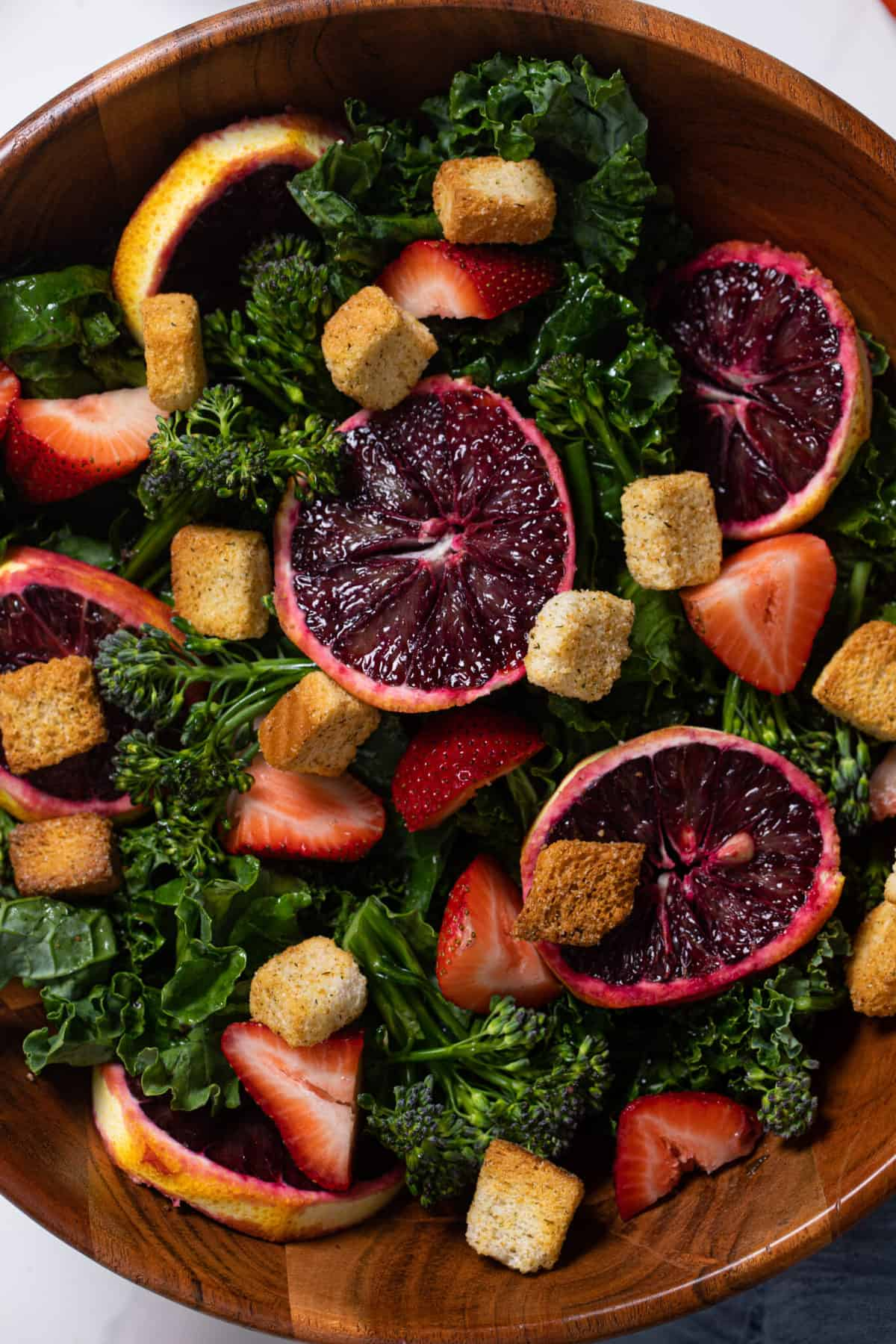 overhead close up of a bowl of blood orange kale salad with strawberries with a gold fork and croutons