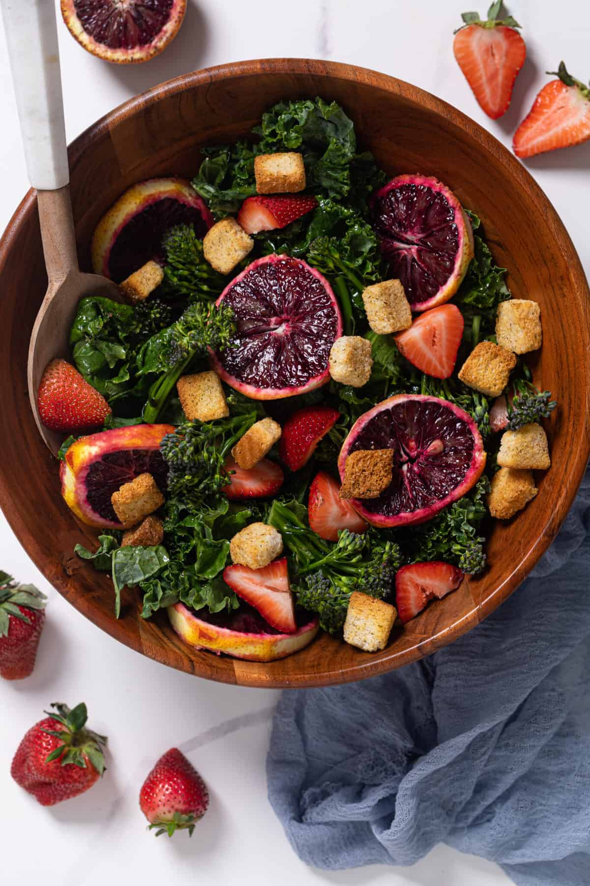 overhead of a bowl of blood orange kale salad with strawberries with a gold fork and croutons and a wooden spoon