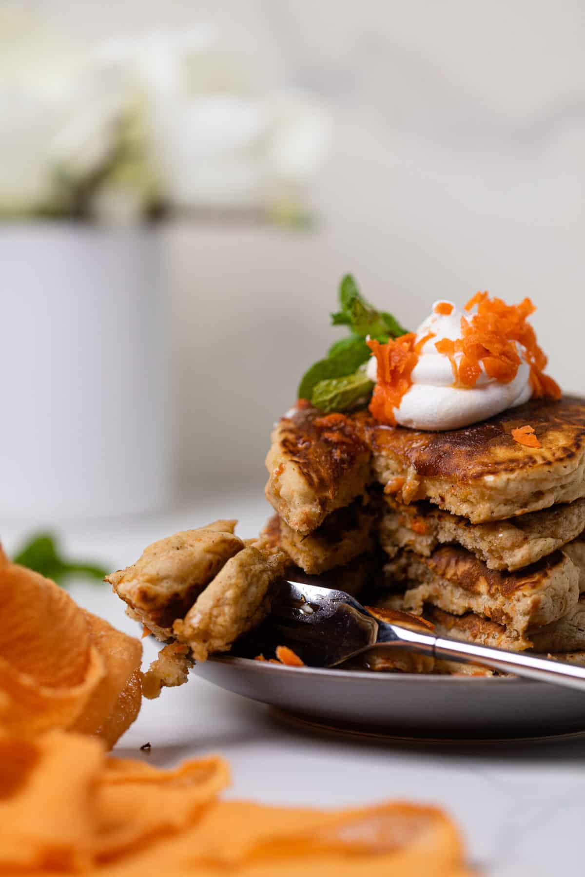 plate of Easy Vegan Carrot Cake Pancakes in a stack with coconut cream and carrots on top