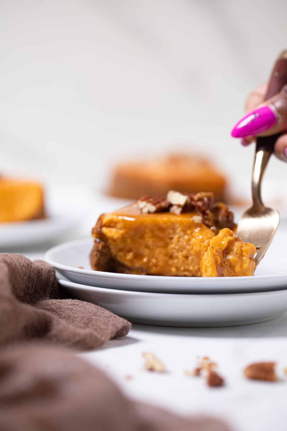 slice of sweet potato cheesecake with a hand taking a bite on a white plate