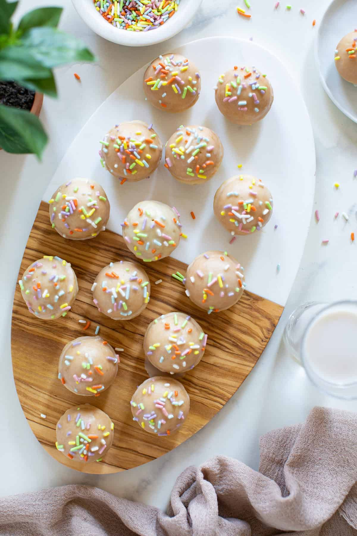 overhead of cutting board with vegan sprinkle donut holes with rainbow sprinkles