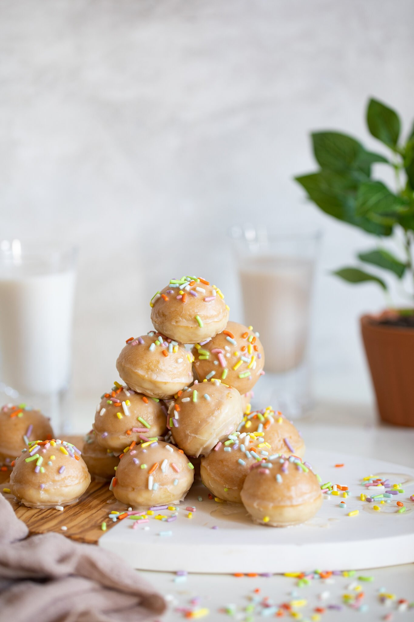 stack of vegan donut holes with sprinkles and vanilla glaze on a cutting board