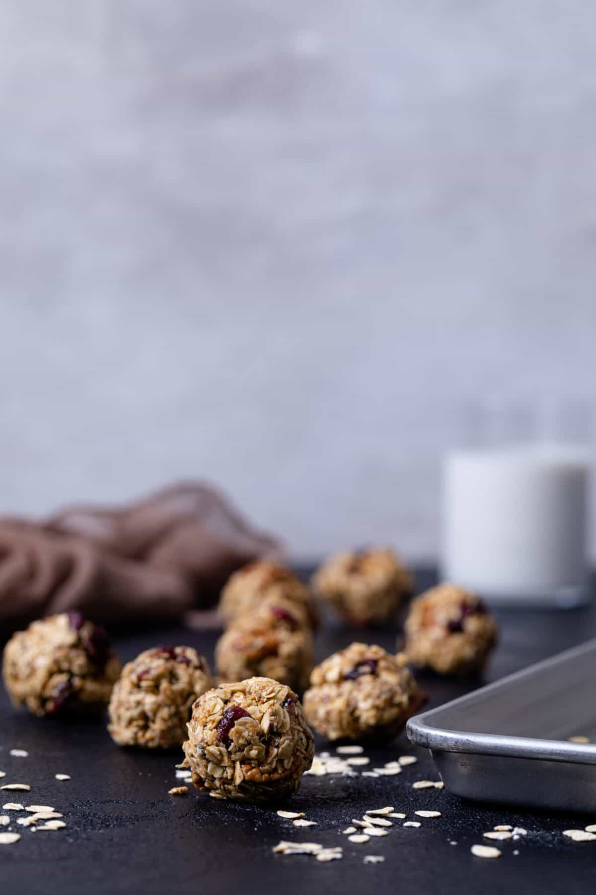 White Chocolate Cranberry Energy Bites next to a baking dish on a black table