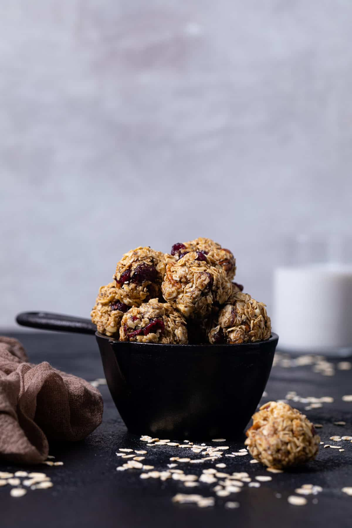 White Chocolate Cranberry Energy Bites in a black measuring cup on a black table