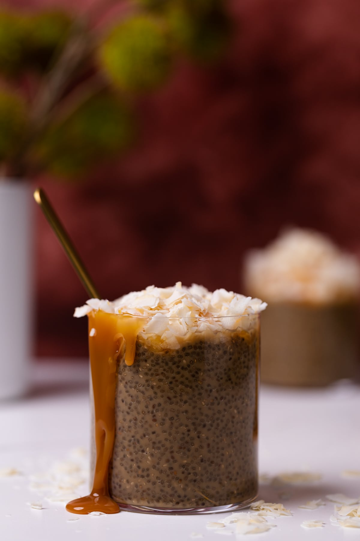 Caramel Macchiato Chia Pudding + Coconut with caramel sauce dripping down the side