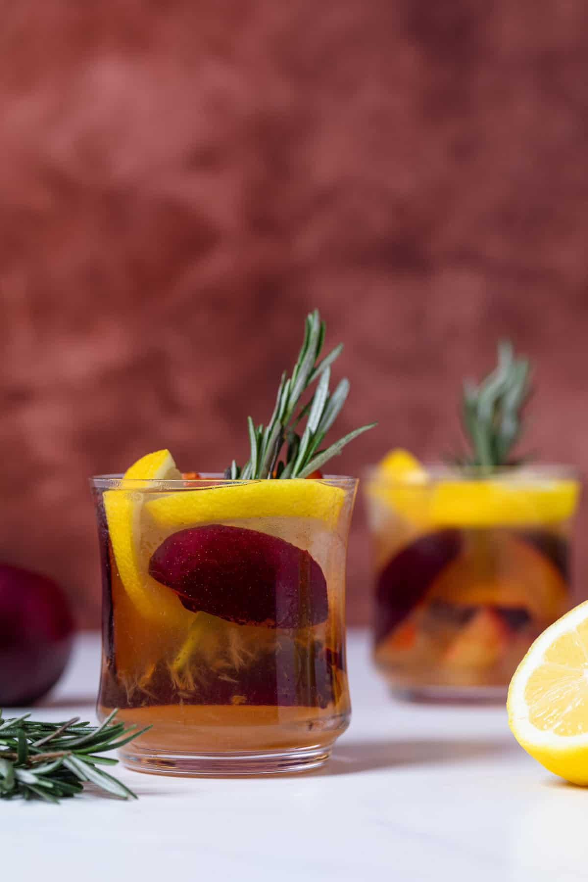Plum Lemonade in a glass with rosemary and fresh fruit