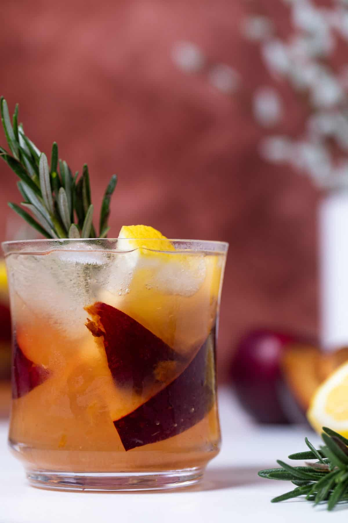 Plum Lemonade in a glass with fresh fruit and rosemary