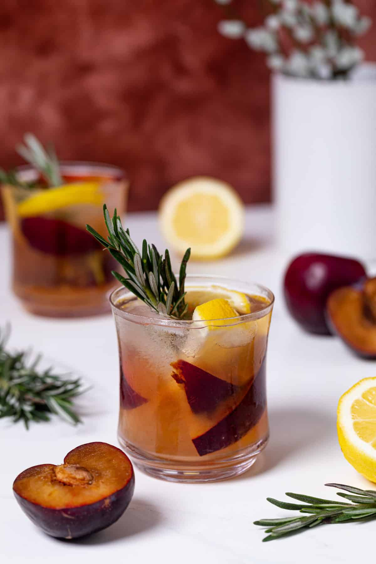 Plum Lemonade in a glass with rosemary and cut up fruit around