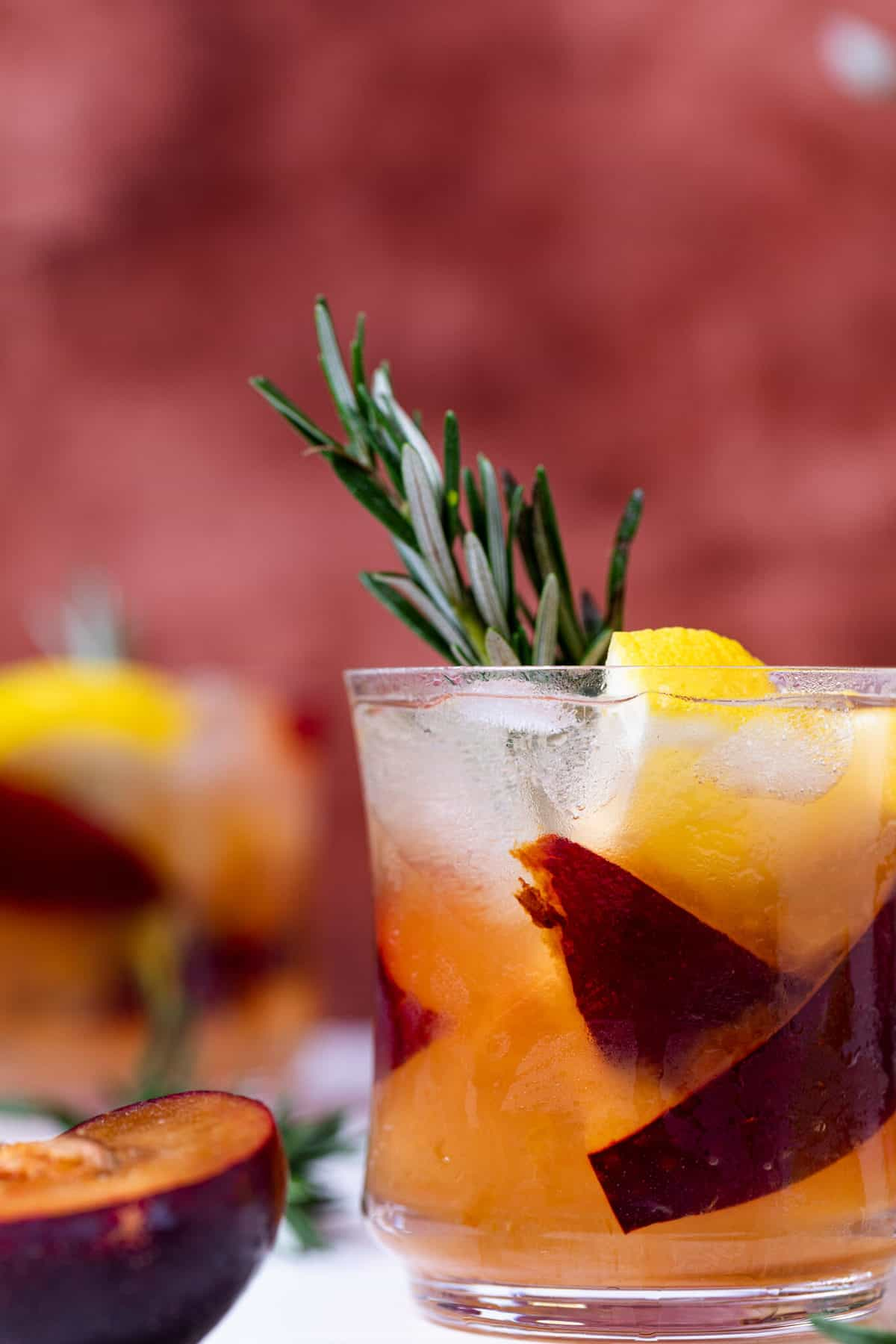 glass of Plum Lemonade with fresh fruit and rosemary