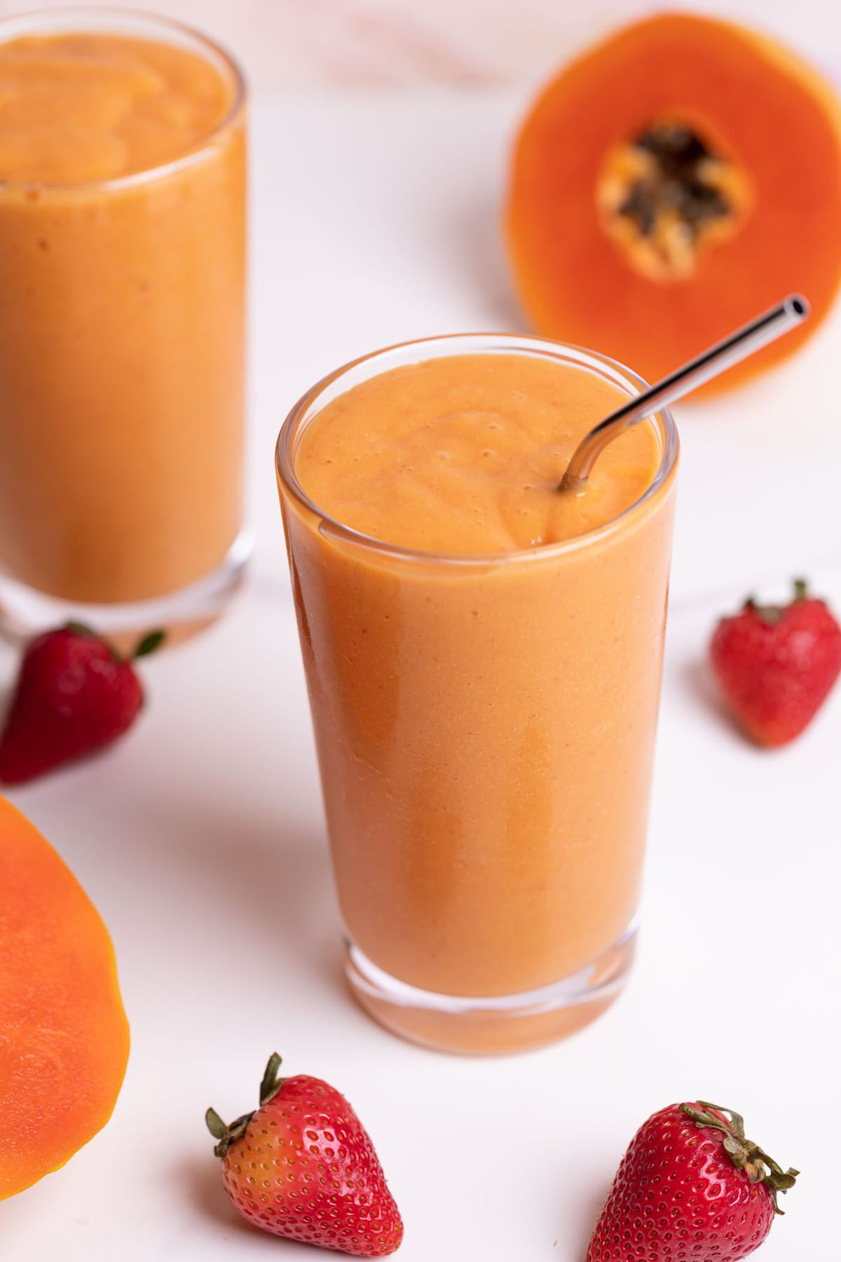 two glasses of papaya smoothies with fresh strawberries on the side