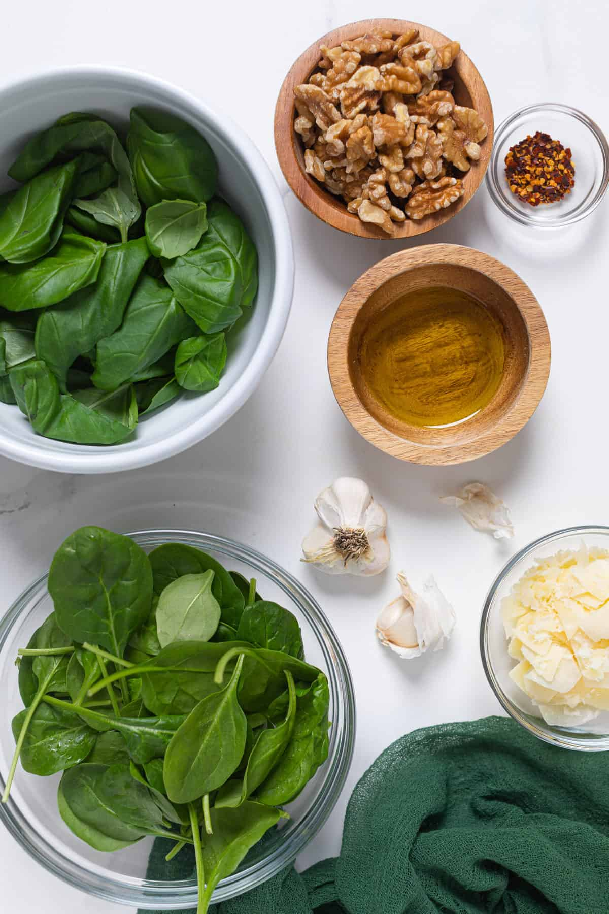 bowls of raw spinach, basil, walnuts, olive oil, garlic cloves and parmesan cheese