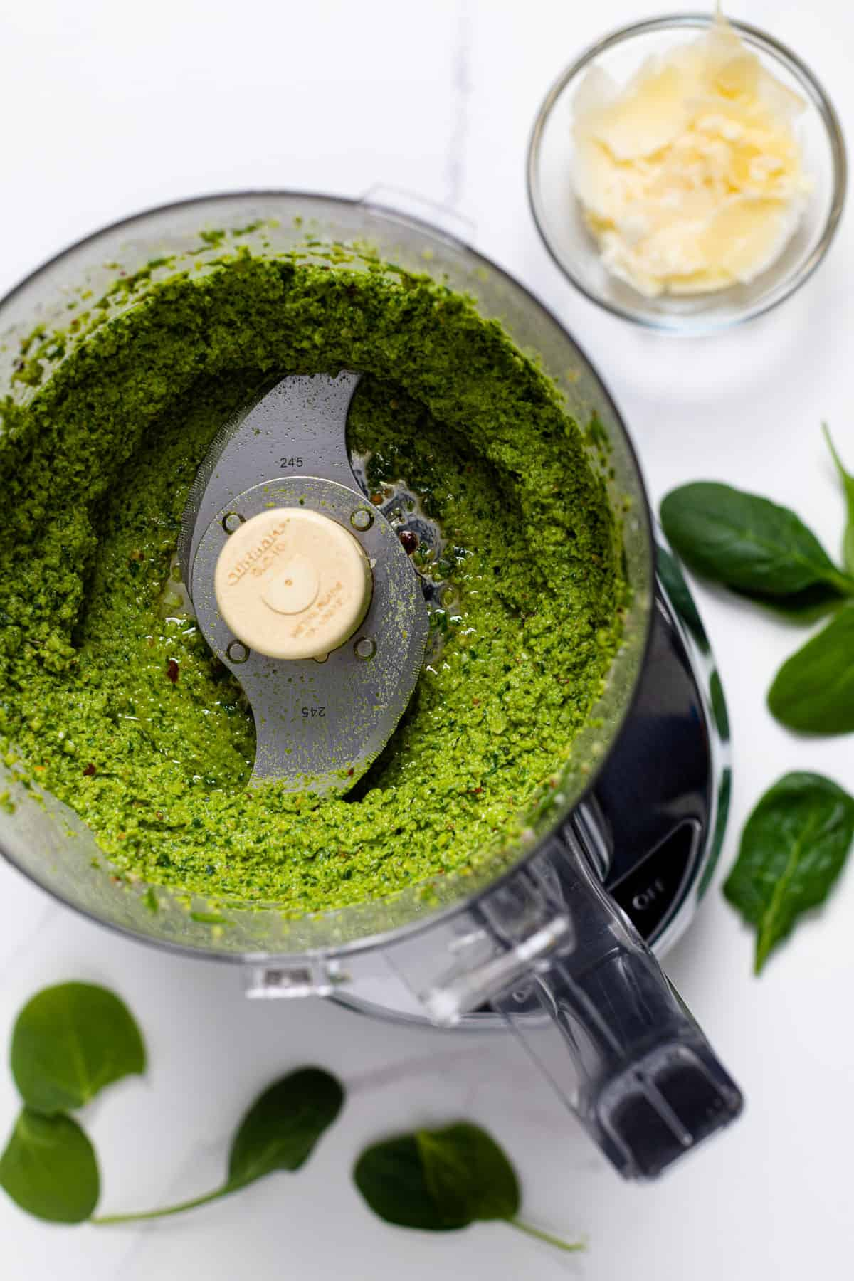Pesto sauce in a food processor with spinach leaves on the counter