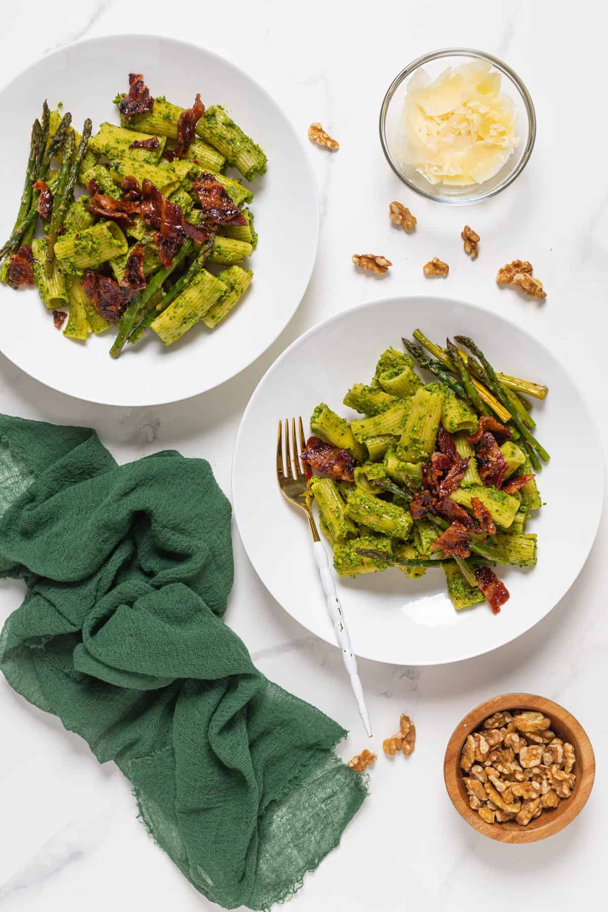 Pesto Pasta with Asparagus + Bacon on two white plates with a gold and white fork