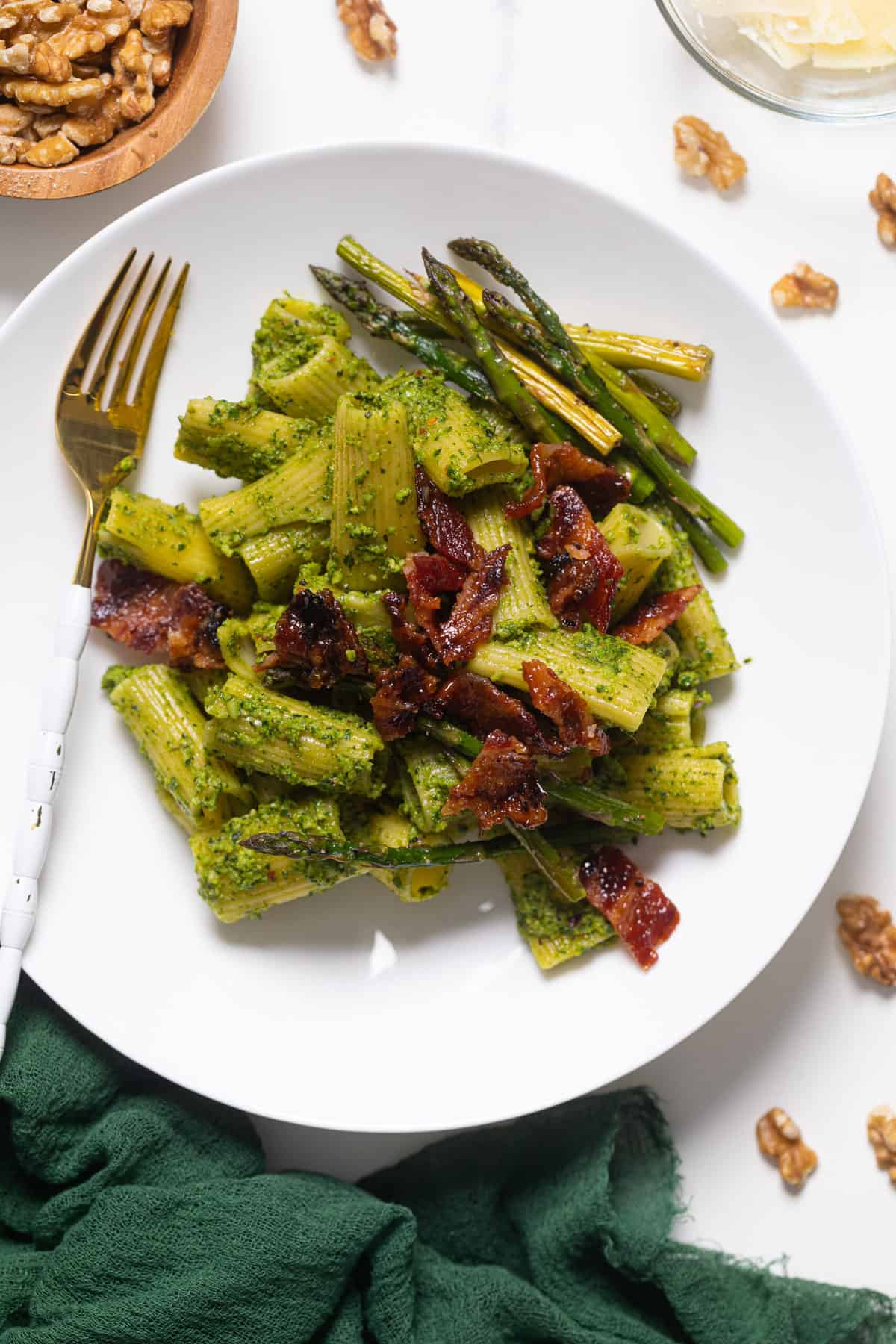 Pesto Pasta with Asparagus + Bacon on a white plate with a gold and white fork